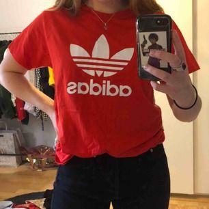 Röd adidas originals T-shirt med ascoolt originals tryck på ryggen! Storleken är Herr S, passar bra på mig som brukar ha M.