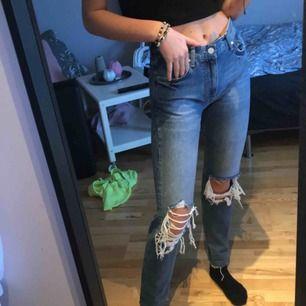 Blåa slitna raka jeans