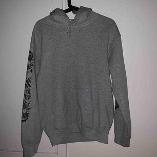 Mysig grå hoodie i fint skick. Svarta detaljer på ärmarna och bak på luvan.