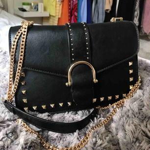 Fin svart väska med snygga gulddetaljer! Använd fåtal gånger, fint skick