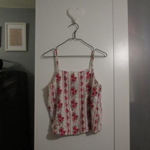 Vitt linne med rosor som är köpt på H&M, inte använd så ofta och i bra skick. Frakt ingår!