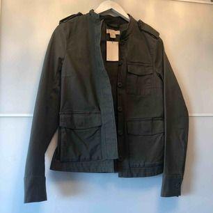 Säljer denna mörk gröna jacka från Hm. Aldrig använd med prislappen kvar. Jackan har snygga detaljer och är i storlek 34. Frakt tillkommer om du ej kan mötas upp i centrala Stockholm.