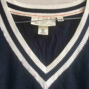 En finstickad tröja från H&M, L.O.G.G. Tröjan är v-ringad och marinblå med vita ränder i muddarna och runt halsen. Mycket bra skick! Frakt tillkommer