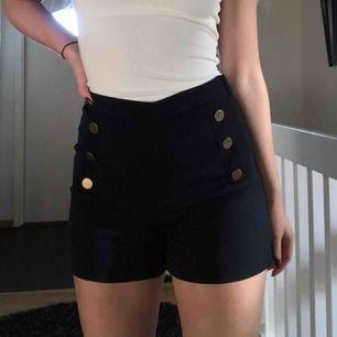 """Snygga marinblå shorts med """"fejk""""-knappar fram."""