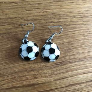 Fotbolls örhängen, aldrig använt, till tjejer och killar som gillar fotboll, man betalar frakt själv. Som en halv fotboll ser dom ut, svarta vita med silver på. 100% metall. Kom gärna med egna pris