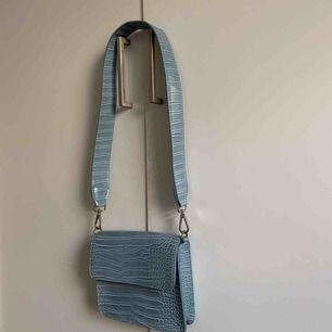 Jättefin väska från HVISK, supertrendig modell. Ljusblå fräsch färg, och bandet är något kortare så den sitter snyggt tvärsöver. Väskan är i nyskick, använd 1 gång. Nypris 750kr. Frakt tillkommer.