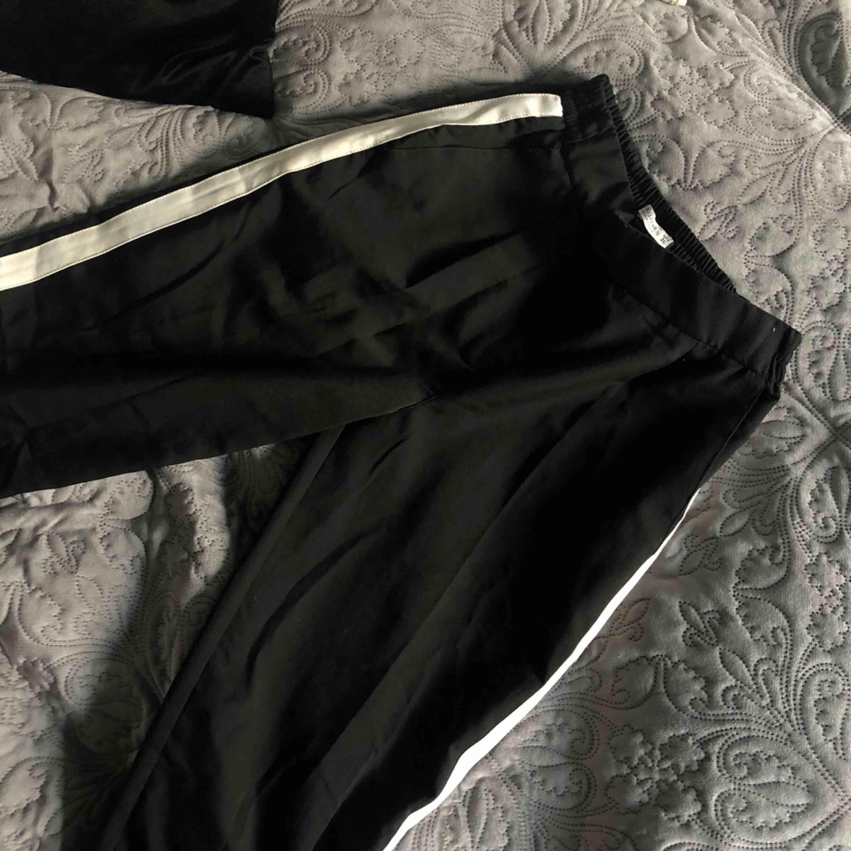 Coola svarta kostymbyxor med vit rand på sidorna! Använd max en gång och är i nyskick som när den var köpt!🥶  (Priset kan diskuteras);). Jeans & Byxor.