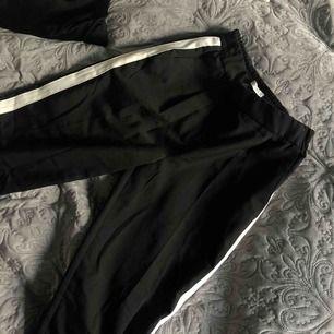 Coola svarta kostymbyxor med vit rand på sidorna! Använd max en gång och är i nyskick som när den var köpt!🥶  (Priset kan diskuteras);)