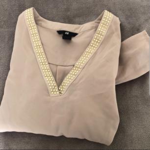 Färg: beige Strl: 36  Snygg blus från H&M. Guld-detaljer framtill. Passar både vardags & fest! Finare i verklighet än på bild..! Använd vid ett tillfälle, dvs mycket gott skick!  Kommer ej till användning och stor garderobsrensning pågår! 150 kr inkl frakt.