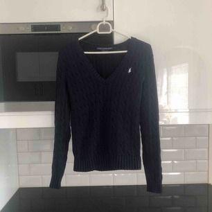 Klassiska Ralph Lauren cable knit sweater, fin marinblå färg och söt urringning! Fint skick. Perfekt för ivy-looken :) Blåare i verkligheten!