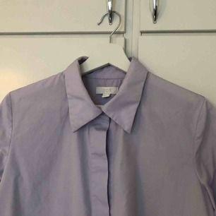 Syrenlila skjorta från COS i storlek 36. Skjortan är A-linjeformad så den är större nertill och mer figursydd upptill. Aldrig använd av mig, endast tvättad en gång. Avklippta detaljer. I perfekt skick! Frakt 63kr/upphämtning Södermalm