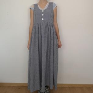 Superdupersöt retro h&m-klänning som mäter cirka 132 cm mätt från axelsömmen ner till kjolslutet. Rakt över bröstet mäter den cirka 45 cm, mätt liggandes platt på marken. Har söta stora knappar fram som går att öppna. Ingen dragkedja på sidan utan endast öppningen via de tre knapparna. I vitt och blått rutmönster, väldigt fint skick! Frakten för denna ligger på 63 kr, samfraktar gärna! 😌👍