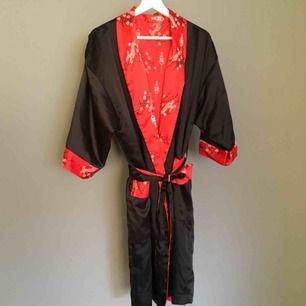Kimono som går att vända ut och in, så den blir röd med mönster istället för svart med broderi där bak, föreställande en drake.   Tyvärr ett ciggbrännmärke på den röda kanten på ärmen. Kan skicka bild vid intresse.