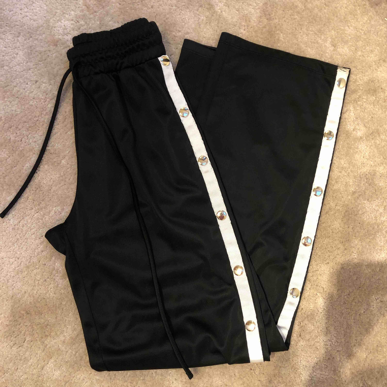 Svarta lösa byxor från chiquelle med guldiga knappar på sidorna som går att knäppa upp. Frakt tillkommer! . Jeans & Byxor.