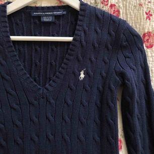 Marinblå kabelstickad tröja från Ralph Lauren. Använd men fin. Köparen står för frakten.