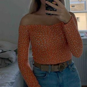 En skit snygg off shoulder tröja men tyvärr aldrig använt. Det är en orange tröja med små vita blommor på sig. Köpare betalar för frakten