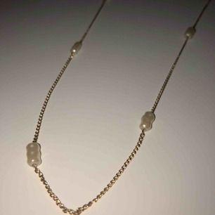 Ett längre guldhalsband (inte äkta guld) med vita stenar. Köparen står för frakten💕