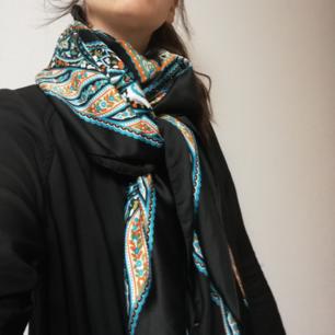 Stor paisley-mönstrad sjal med turkosa, orange och vita mönster på svart botten. Jättelyxig och känns precis som siden men det är nog polyester, den är köpt på Åhléns för något år sedan och lappen är avklippt så kan inte se materialet. Använd ett fåtal gånger bara och i fint skick. Mått 135x135 cm. Frakt 36 kr.
