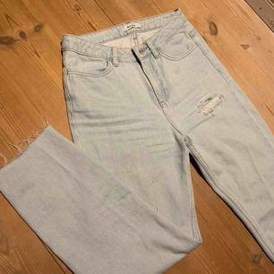 snyggt ljus blå jeans från NA-KD med ett hål på knä