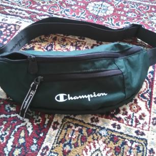 Champion fannypack i skogsgrön som tyvärr aldrig kommer till användning. Frakt ingår