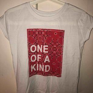 """Suuupersnygg  vit T-shirt med rött """"bandana"""" tryck fram och texten """"one of a kind"""" den är i barnstorlek 134/140 men jag ligger på gränsen till att inte kunna ha den nu. Jag är 16.  Tycker den är så cool och matchar till mycket."""