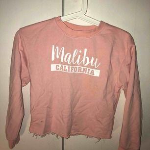 En superfin sweatshirt i barnstorlek. färgen är någon ljusrosa, aprikos.. text på framsidan med Malibu california. Och lite ripped nertill.  Vet att jag använde den i åttan men den är som sagt barnstorlek och beror mycket på längden osv.