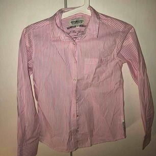 En rosavit randig skjorta. Sitter bra. Barnstorlek 140. Knappt framtill hela vägen upp.