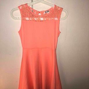 Jättefin aprikos/korall klänning. Spets upp till hela vägen runt och knapp bak. Barnstorlek 146/152