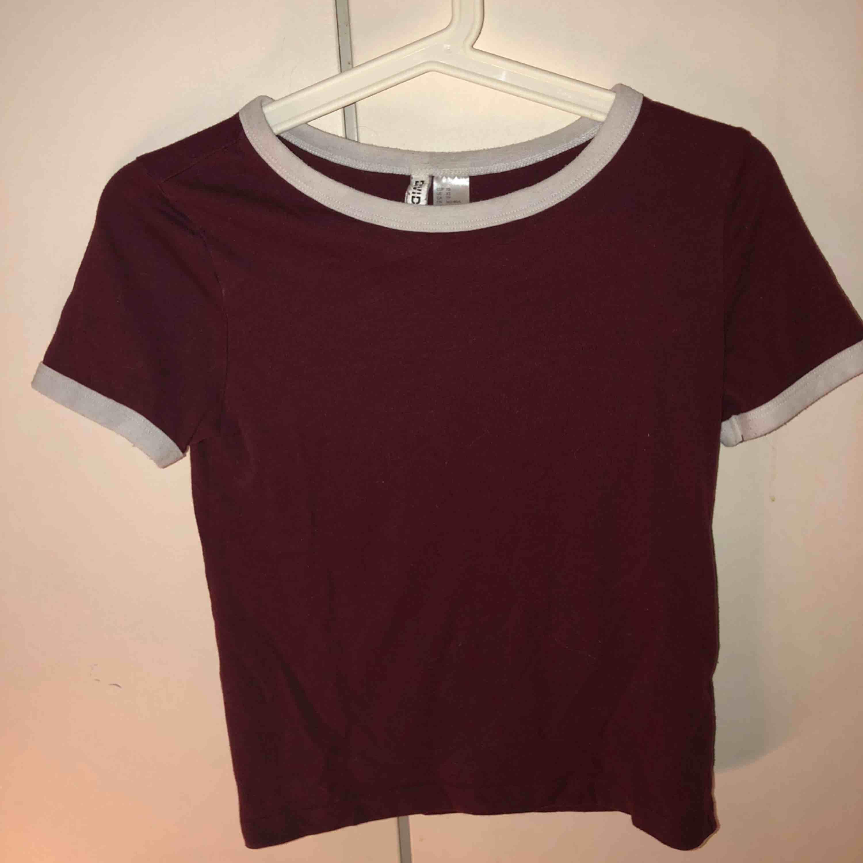Vinröd T-shirt med vita muddar på ärmar och krage. Bra passform och skön.. T-shirts.