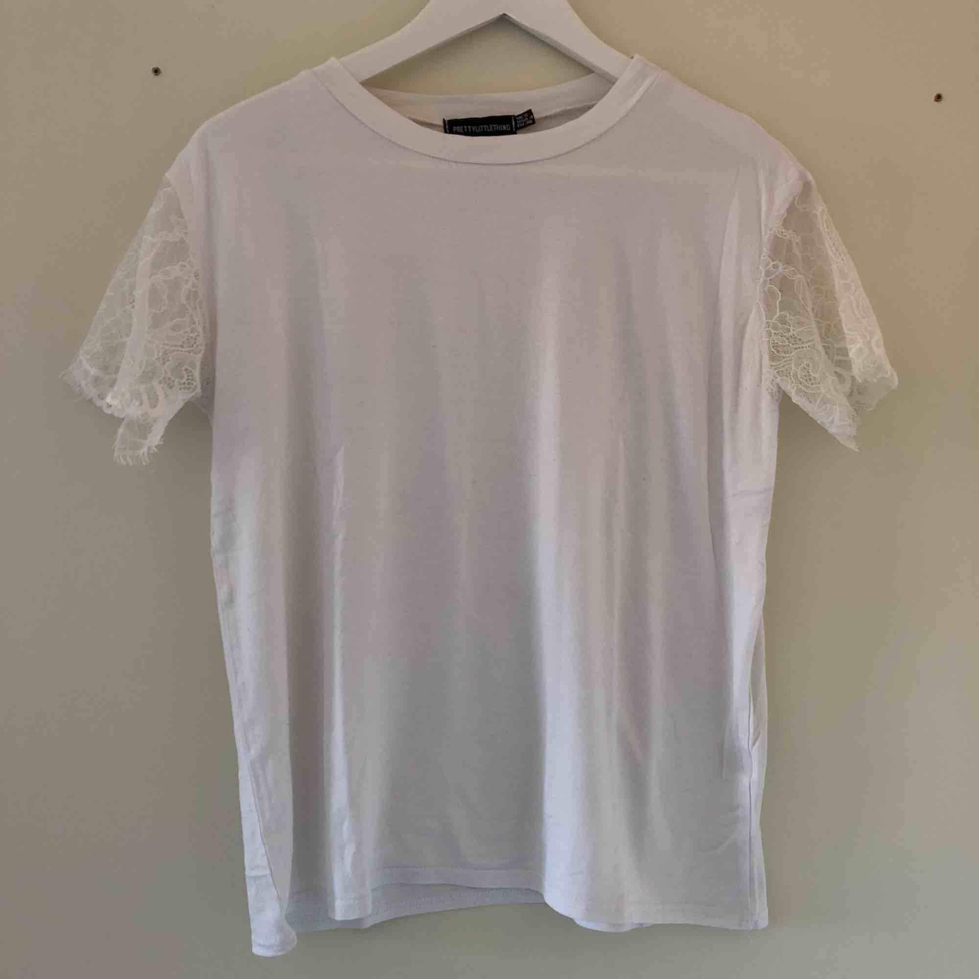 En vit t-shirt med spets armar från prettylittlething i storlek 36. Den är lite stor i storlek och i helhet i bra skick.. T-shirts.