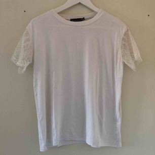 En vit t-shirt med spets armar från prettylittlething i storlek 36. Den är lite stor i storlek och i helhet i bra skick.