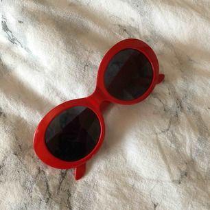 Röda clout brillor med svart glas köpta i New York.