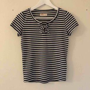 Svart och vit randig t-shirt med knytning i fram från Hollister i storlek S.