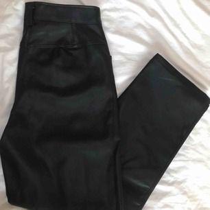 Svarta fakeskinnbyxor från H&M i stuprörsmodell, raka i benen och sitter inte tajt. Använda en gång, bra skick! Köparen står för frakt!✨