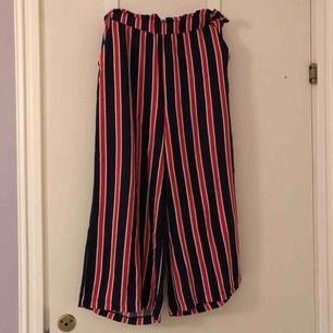 Mörkblå, vit och röd randiga pösiga väldigt sköna byxor från Gina Tricot i storlek 36