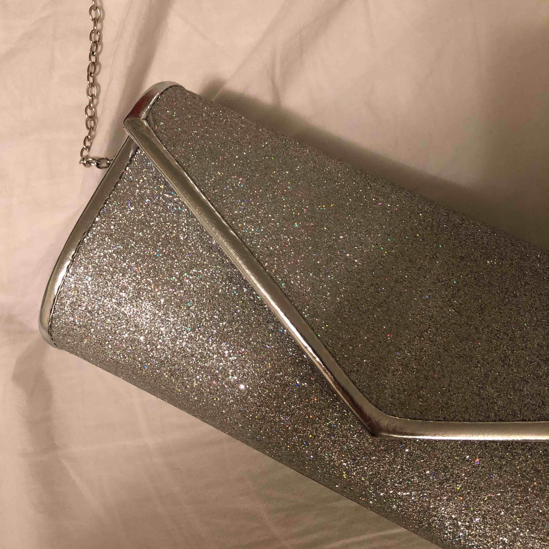 Glittrig silvrig clutch/axelremsväska. Använd en gång!  Kan mötas upp i växjö eller extra fraktkostnad!. Väskor.