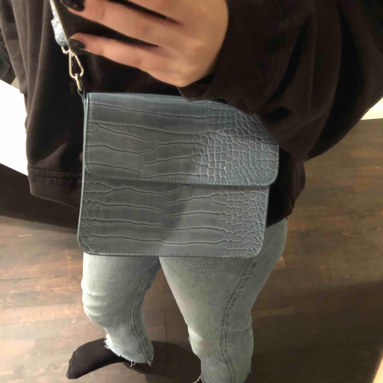 Jättetrendig snygg väska från hvisk! Snygg blå-grå färg. Använt fåtal gånger, är som ny. Nypris ca 750kr, säljer för 350kr💕. Väskor.