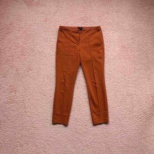 Low waist ankle kostymbyxor i en fin rost röd/orange färg. Väldigt fint nu i höst! De är använda, och i ok skick.
