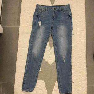 Jeans med lösare passform och slitningar. Boyfriend-jeans modell med mellanhög midja.