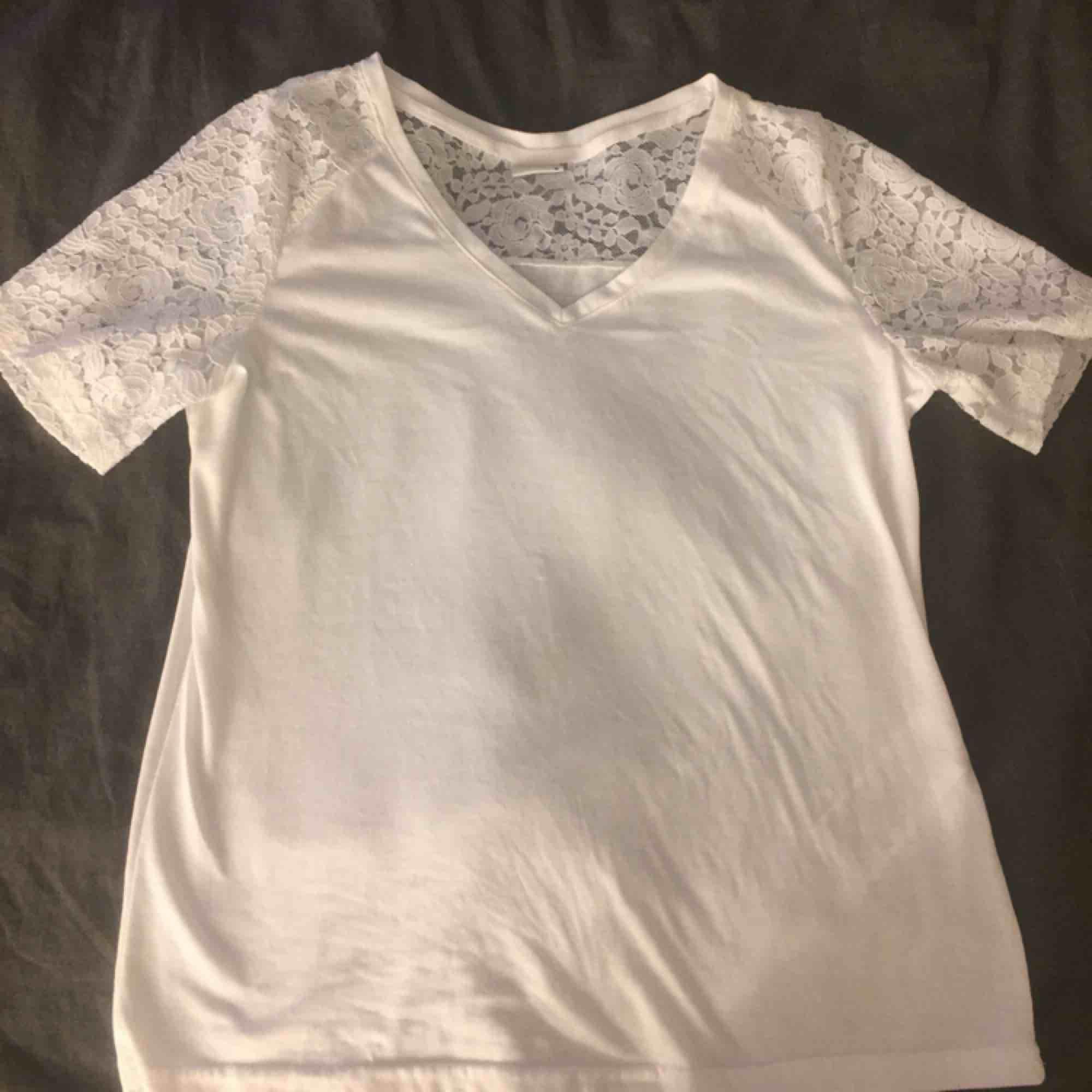 Vit v-ringad t-shirt med spets! Enkel att styla! Det är ett väldigt mjukt material, dock är den genomskinlig. . Blusar.