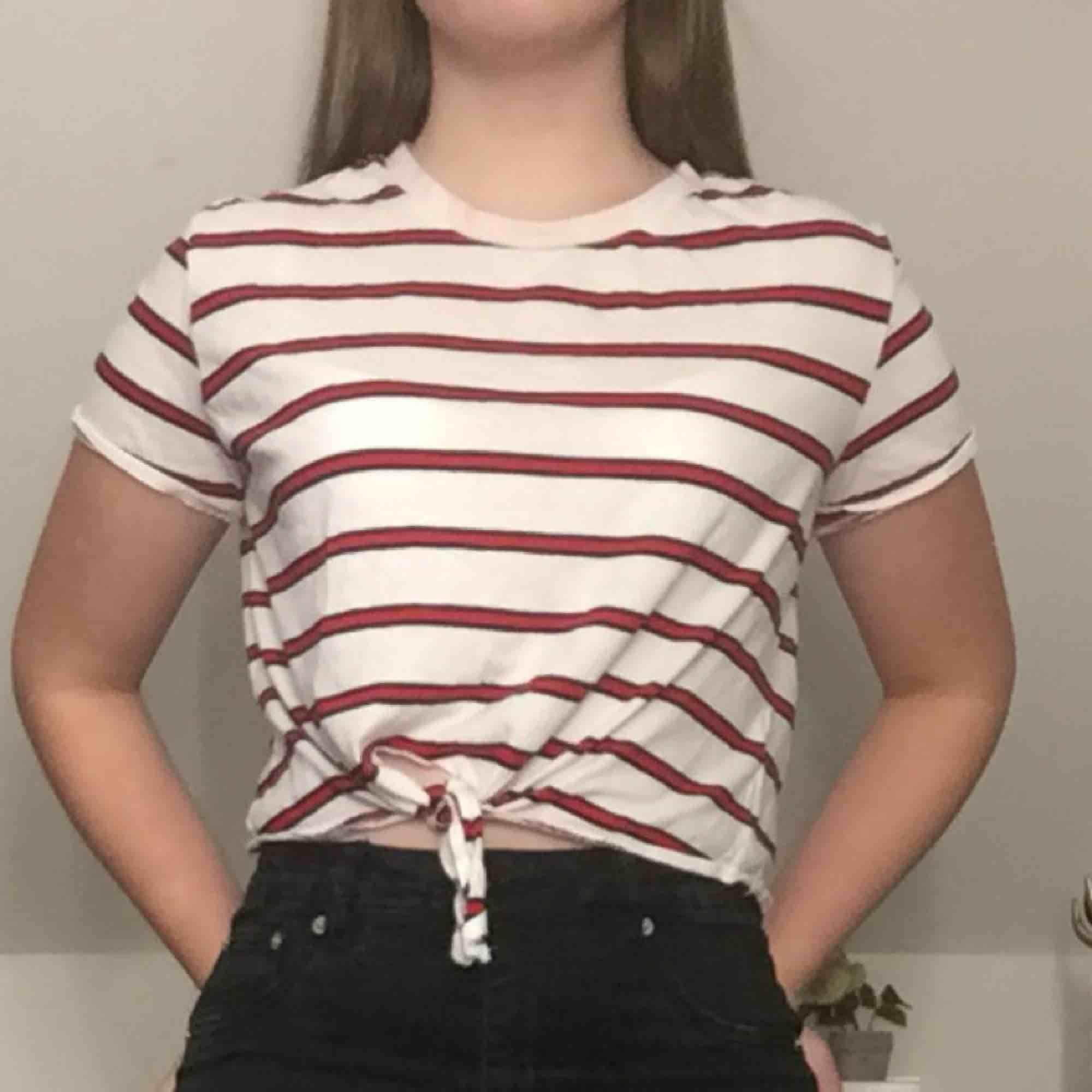Svart-röd randig t-shirt med knytning i bottnen! . T-shirts.