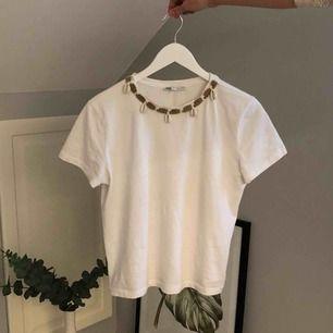 Vit T-shirt från Zara med cool snäck- detalj vid halsen! Köpt i London, storlek S knappt använd. Frakt tillkommer😊