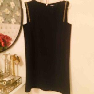 Svart kort klänning med detaljer vid axlarna