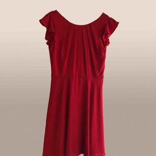 Röd klänning med djup urringning i ryggen. Väldigt klarröd i färgen.