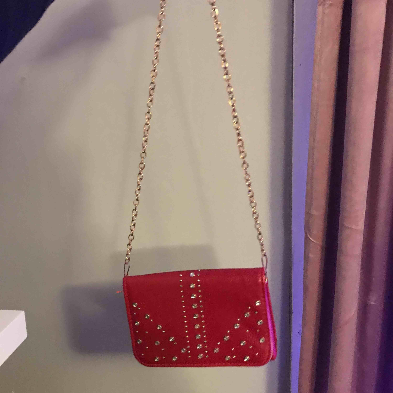 Fin röd handväska med diamanter på med många bra fack i, aldrig använd. Minns inte vart den kommer ifrån står inte heller, Köparen står för frakt 🥰. Väskor.