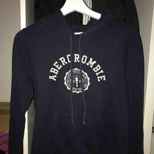 Mörkblå hoodie från Abercrombie & fitch med huva och ficka framtill. Storlek : XS