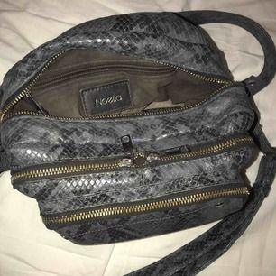 Ormskinnsmönstrad grå väska från Noella. Finns ej längre att hitta på deras hemsida där jag även köpte väskan. Väskan är väldigt rymlig och består av tre fack. Skicket är fint men man kan se lite i insidan att den är använd. Stilren och rymlig!