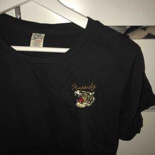 En svart tshirt med broderad tiger på ena bröstet. Storleken är freesize men passar S-M