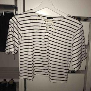 Vit med svart randig t-shirt som är lite kortare i längden. Köpt i Japan och är i perfekt skick! Passar S-M