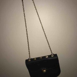 En enkel axelbands väska. Svar med guldigt axelband och guldiga terapier som knäppen och uppepå väskan.